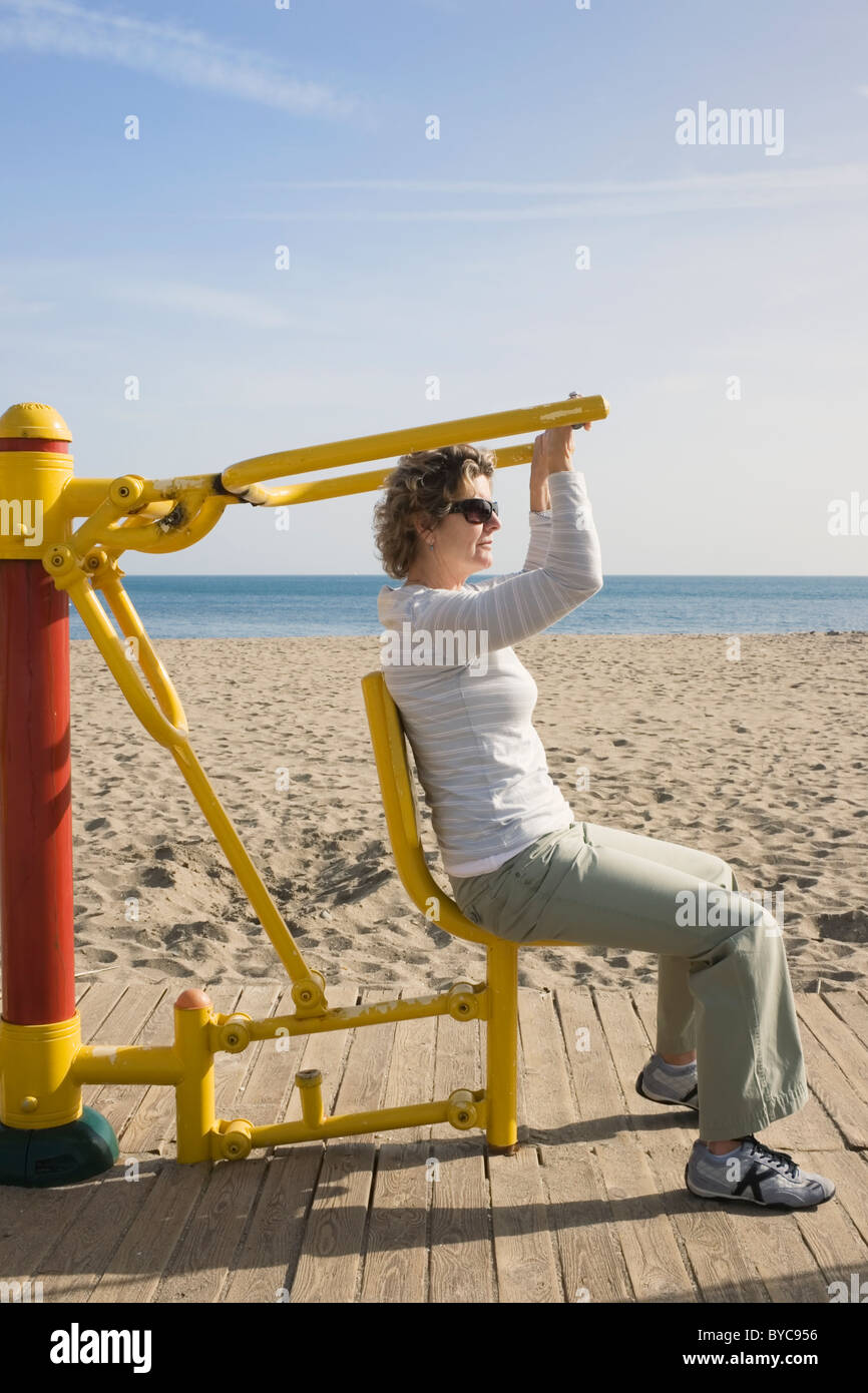 Los Boliches, Fuengirola, Costa del Sol, Spain. Woman using arm excercise machine on beach. - Stock Image