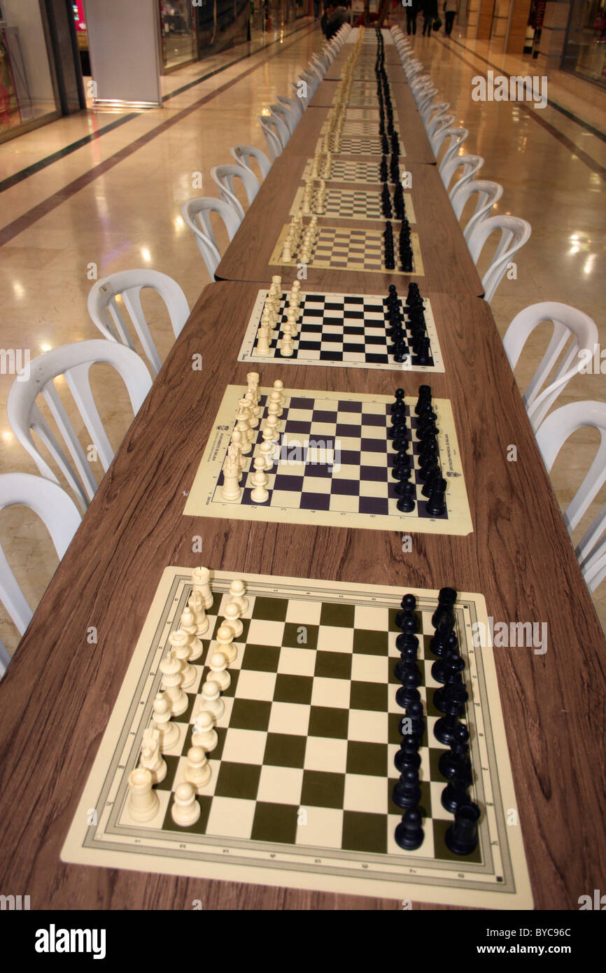Row of chess boards and chess pieces set out for multiple simultaneous games. - Stock Image