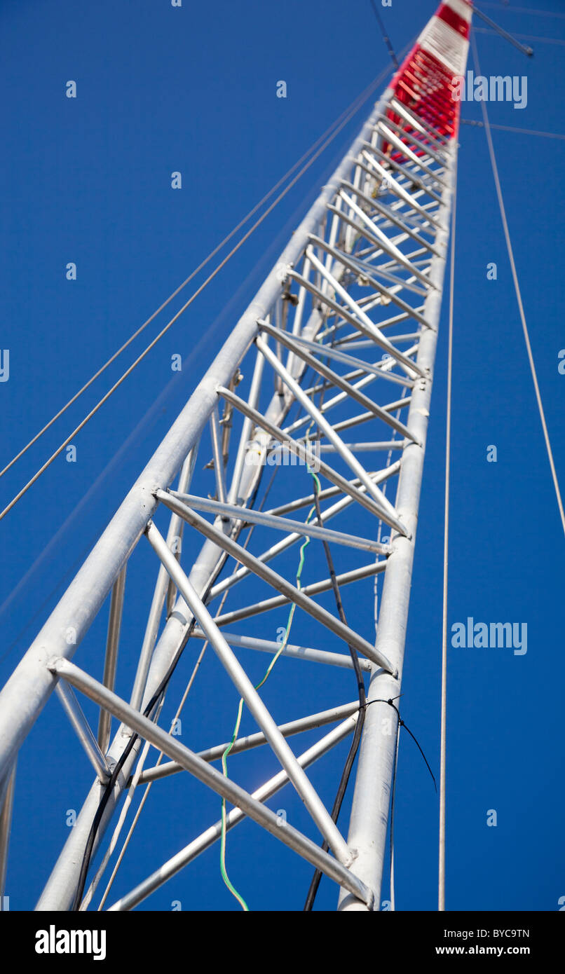 Telecommunication mast structure . Made out of interconnected tubes that form triangular support structure - Stock Image
