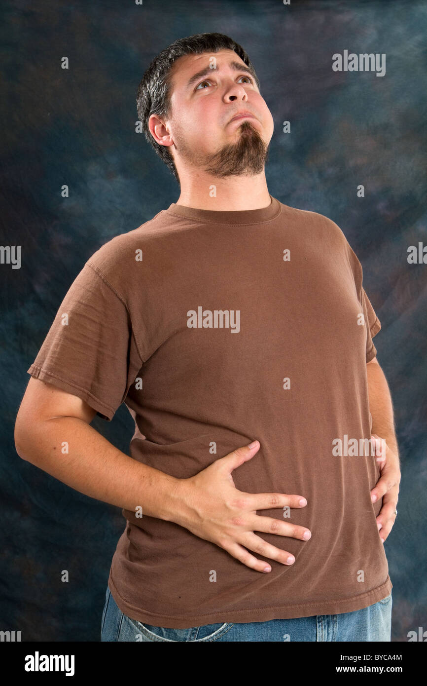 Overweight man holds his stomach after eating too much resulting in indigestion. - Stock Image