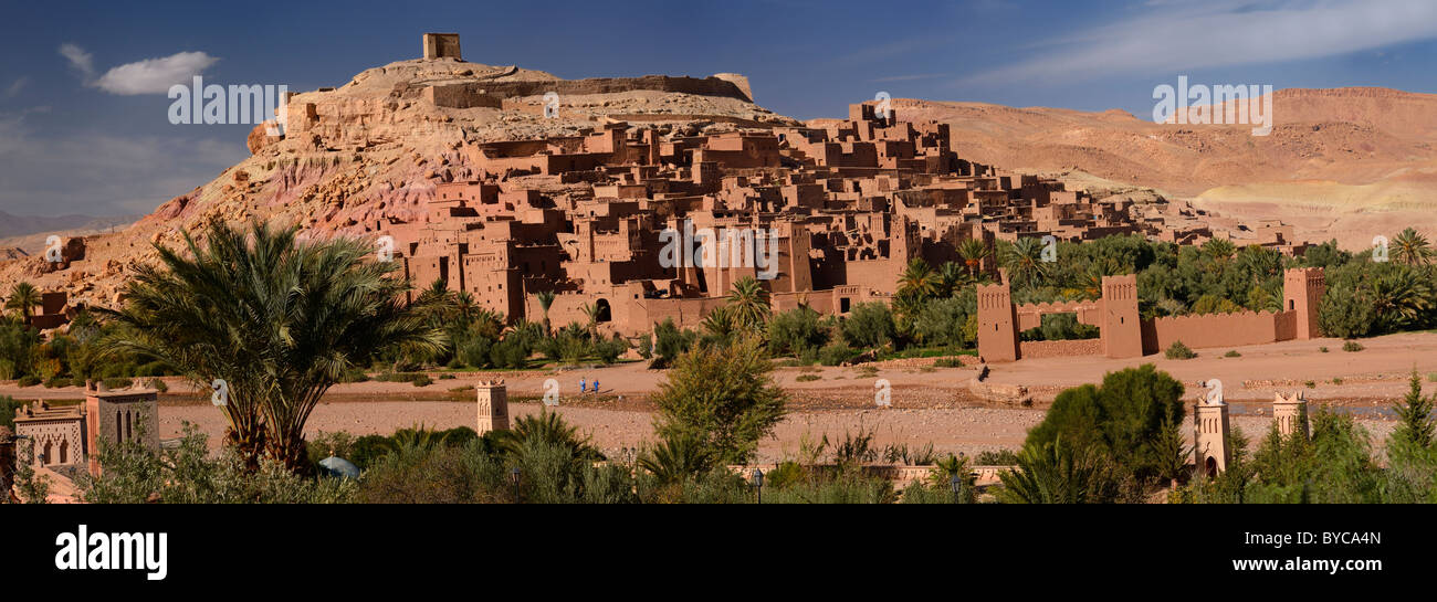 Panorama of ancient city fortress of Ait Benhaddou and blue berbers crossing Wadi Mellah near Ouarzazate Morocco - Stock Image