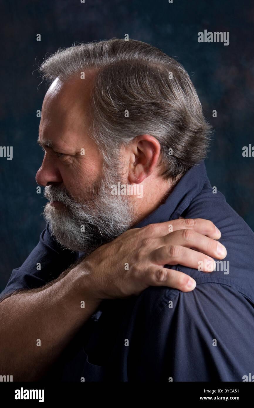 Man massages his painful shoulder. - Stock Image