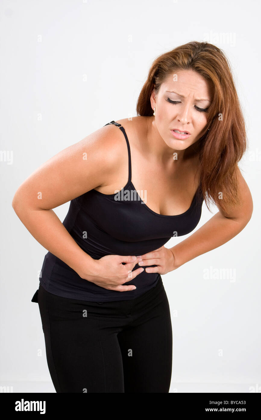 Woman bends over in pain for stomach cramps. - Stock Image