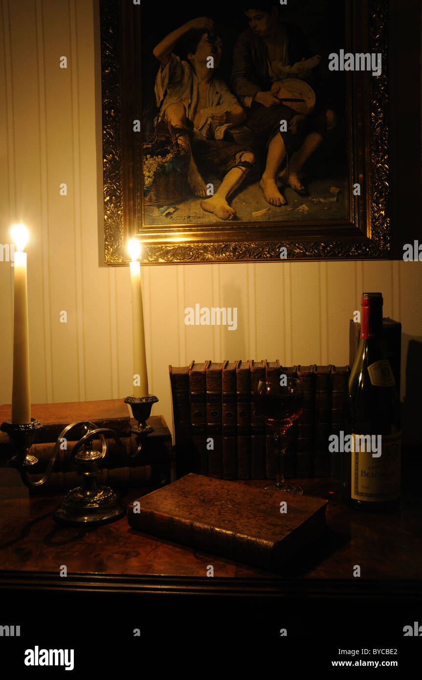 Antiquarian books and wine lit by candlelight - Stock Image