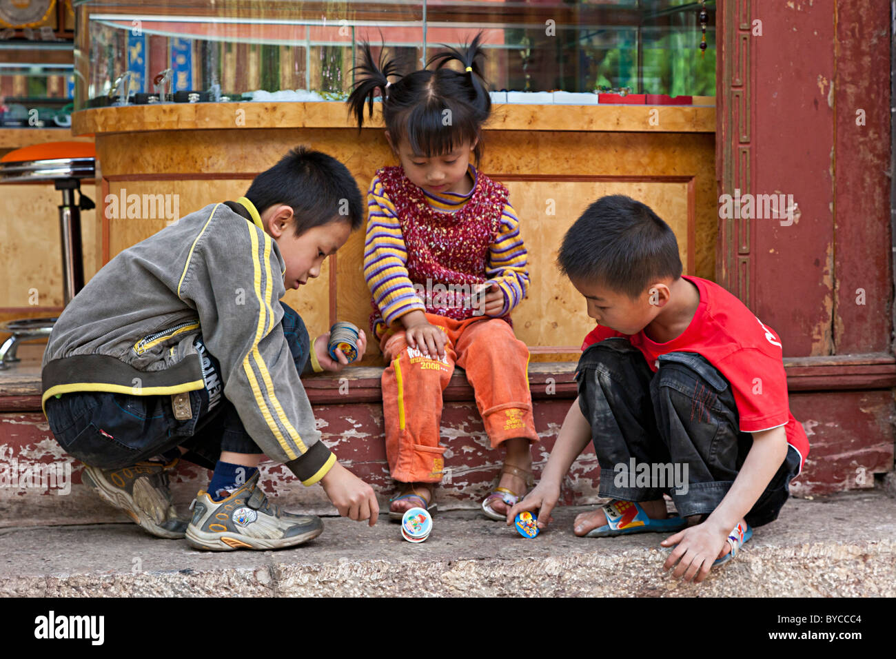 Young children playing game in the Old Market Square, Lijiang, Yunnan Province, China. JMH4751 - Stock Image