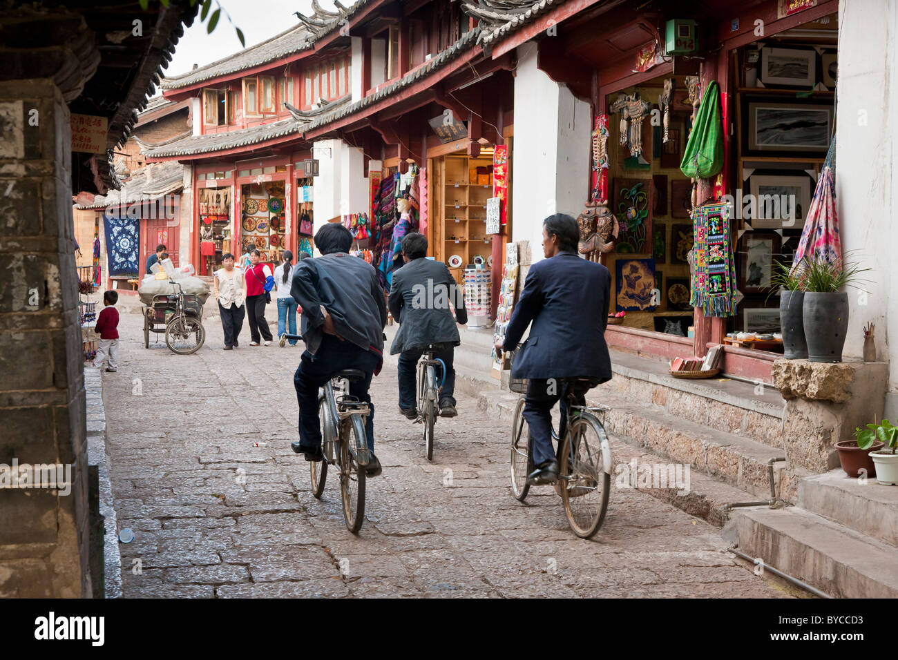 Three men cycling through a narrow paved lane in Lijiang old town, Yunnan Province, China. JMH4755 - Stock Image