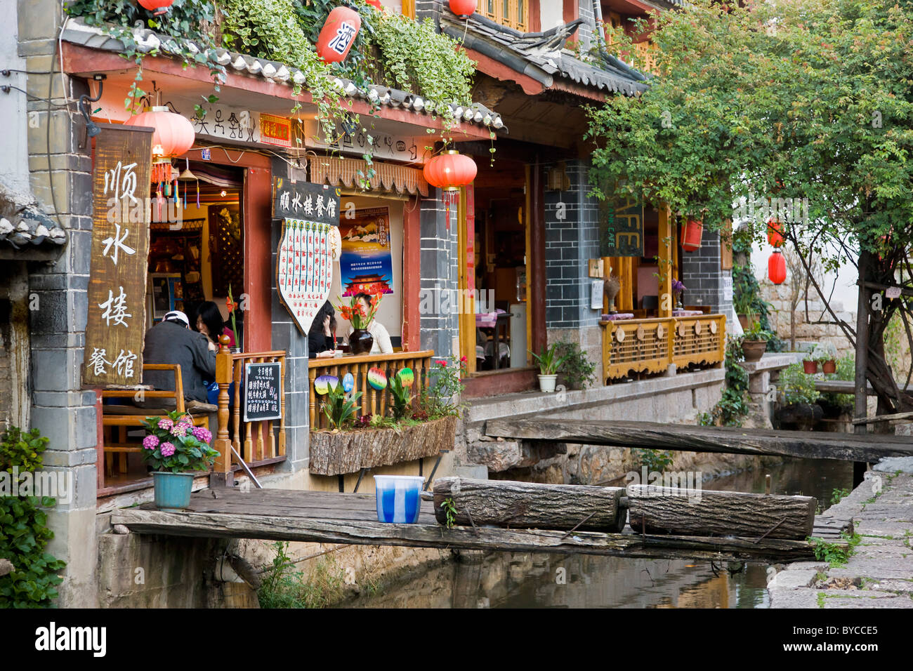 Restaurant bordering stream with small bridges in Lijiang old town, Yunnan Province, China. JMH4759 - Stock Image