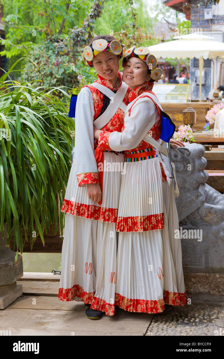 Two young Naxi women in traditional costume in Lijiang old town, Yunnan Province, China. JMH4767 - Stock Image