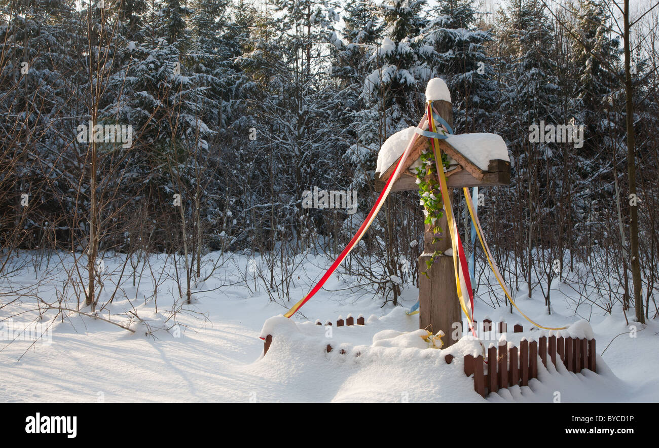 Old wooden cross snow wrapped by road against young spruces in snow - Stock Image