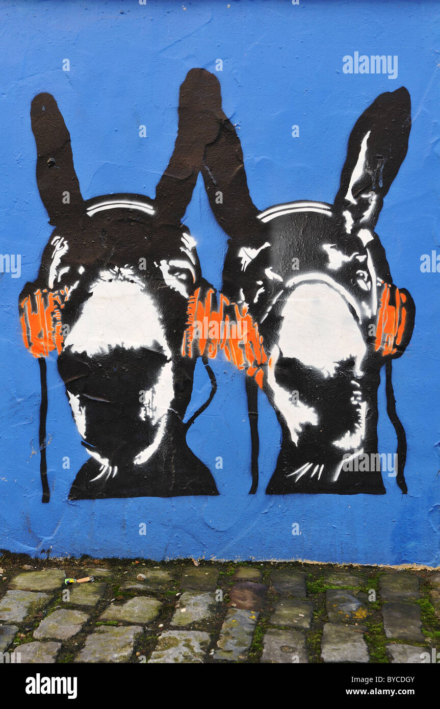 Stencil graffiti in Bristol England depicting donkeys listening to music on headphones - Stock Image