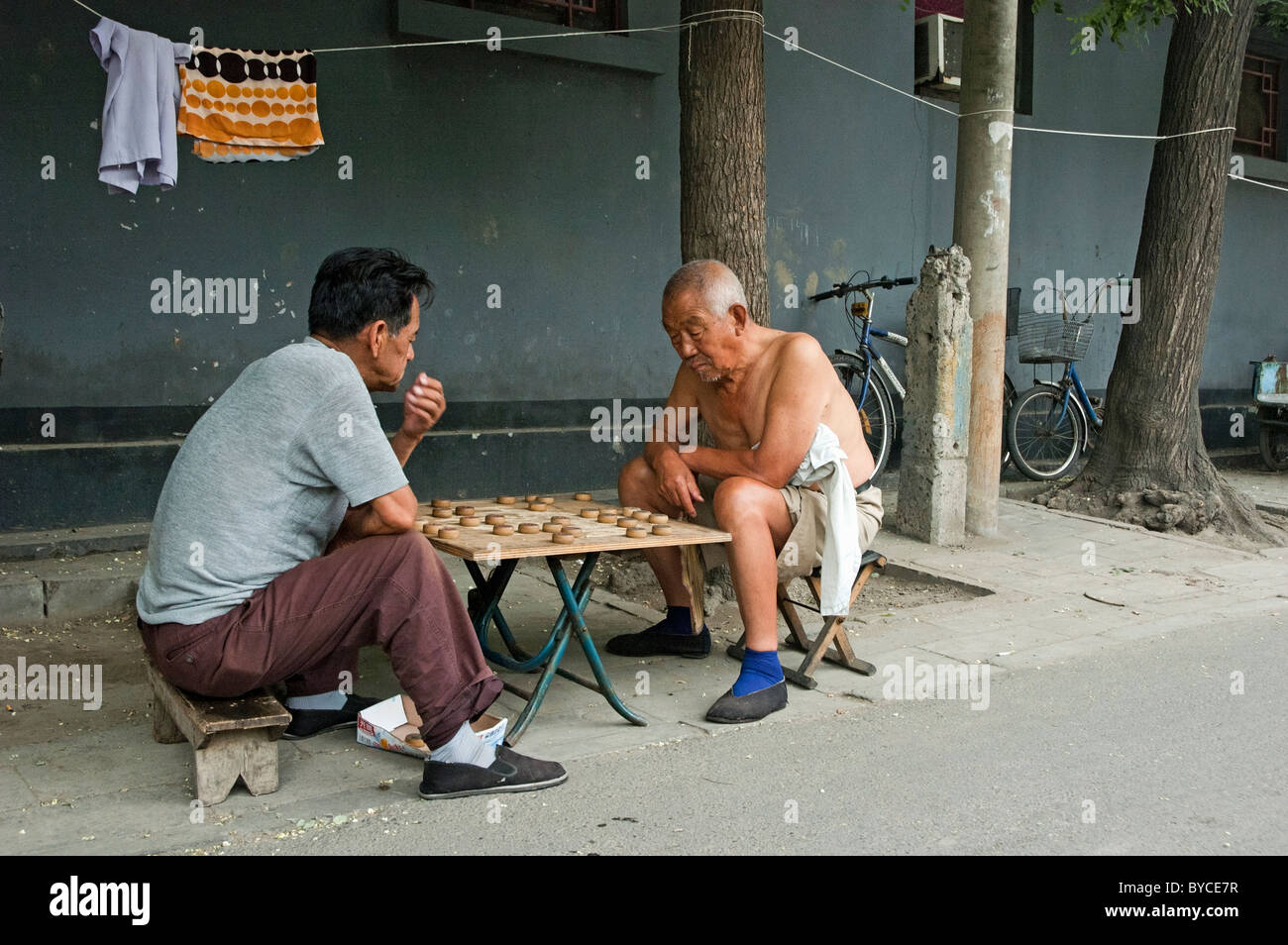 Old men playing Xiangqi or Chinese Chess in Hutong District of Beijing, China - Stock Image