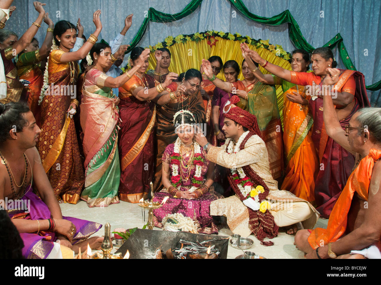 Guests throw rice grains over a newly married couple to symbolize abundance and good fortune at a Hindu wedding - Stock Image