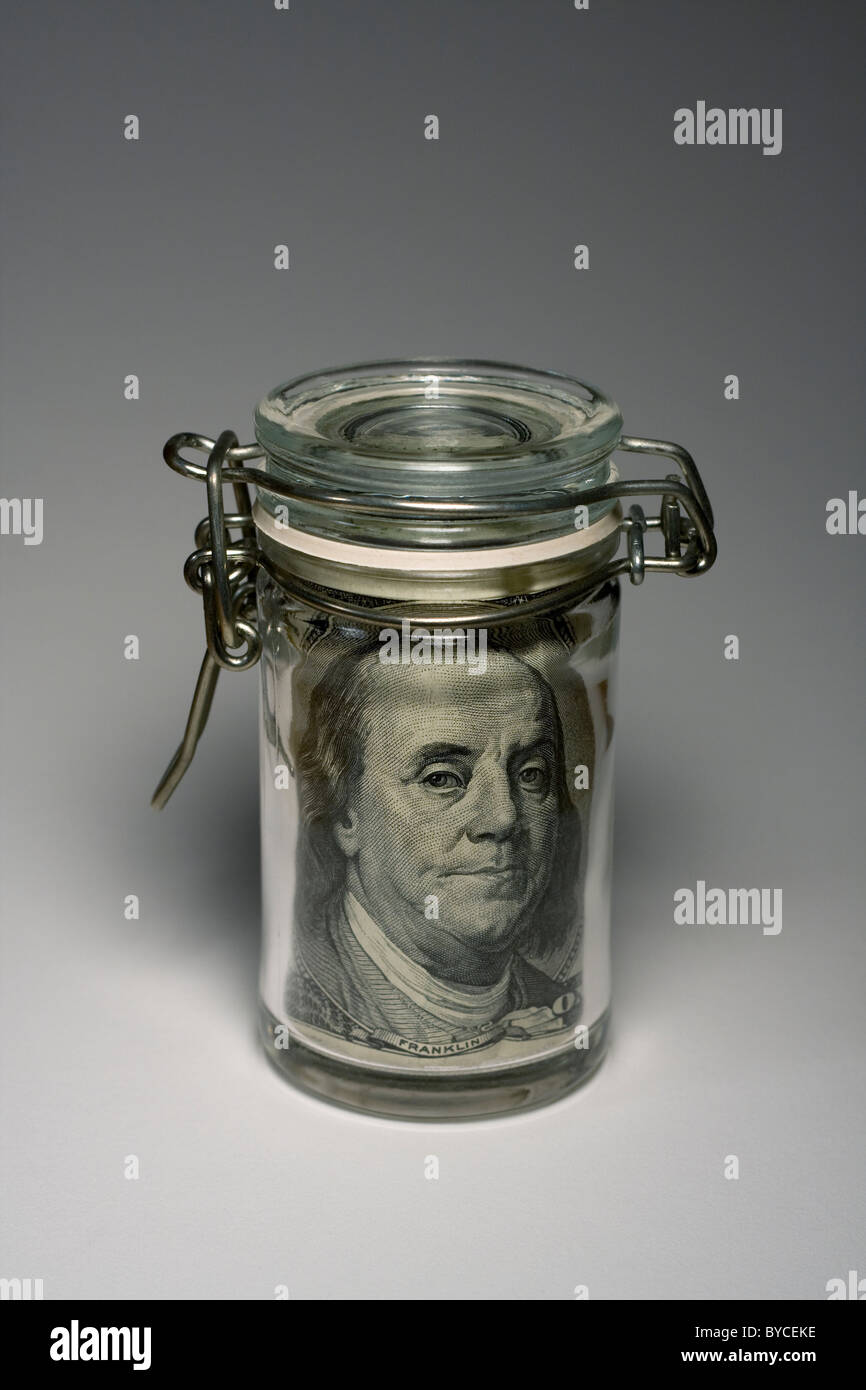 Mason Jar with a $100 bill inside showing Benjamin Franklin's face. - Stock Image