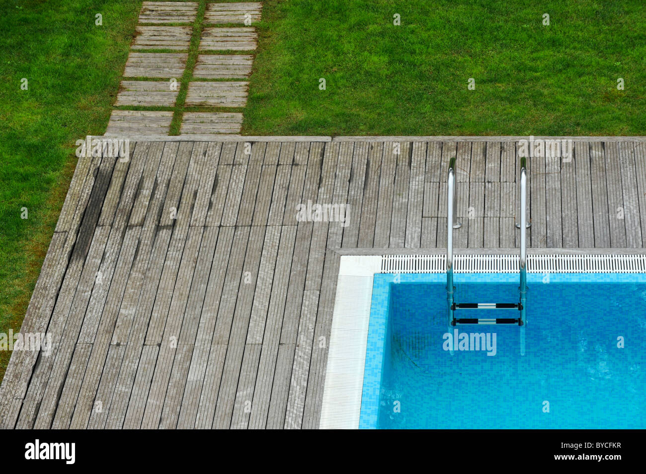 Aerial view of an outdoor swimming pool with wood deck and lawn Stock Photo