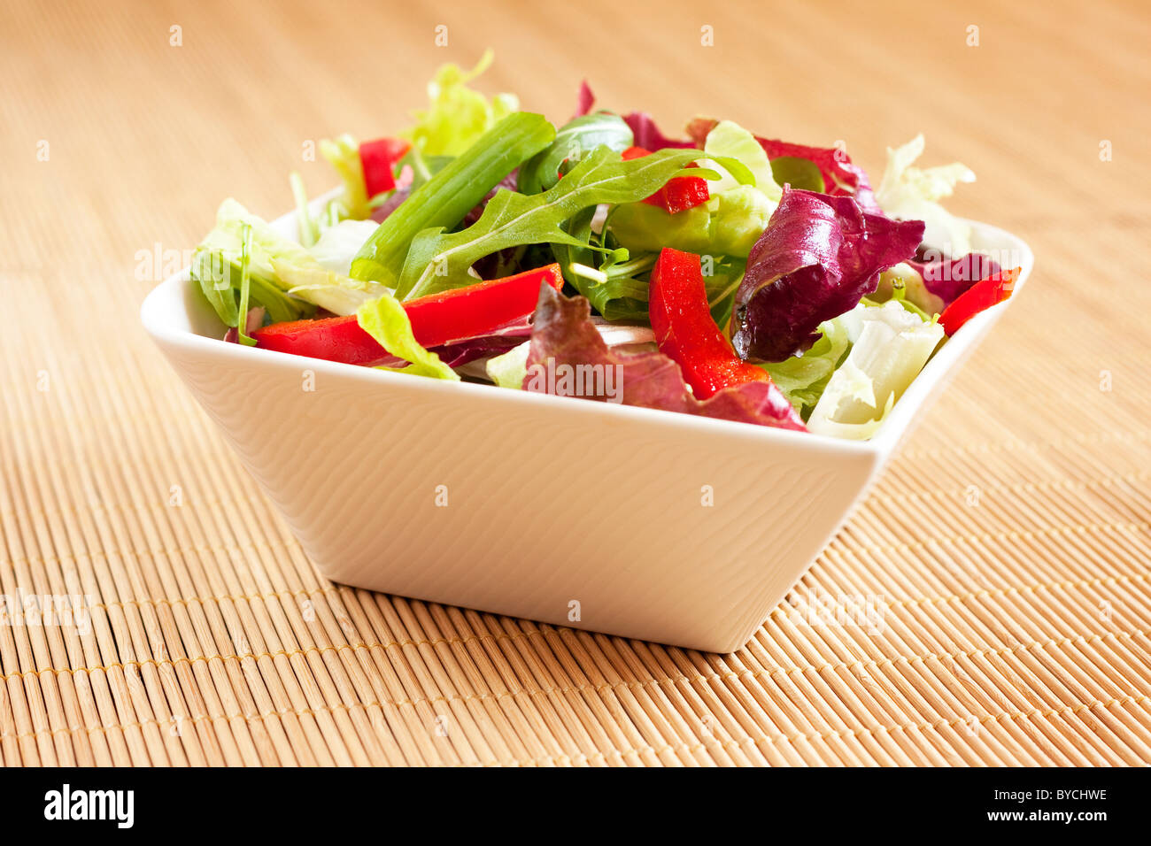 Bowl with mixed salad on bamboo place mats - Stock Image