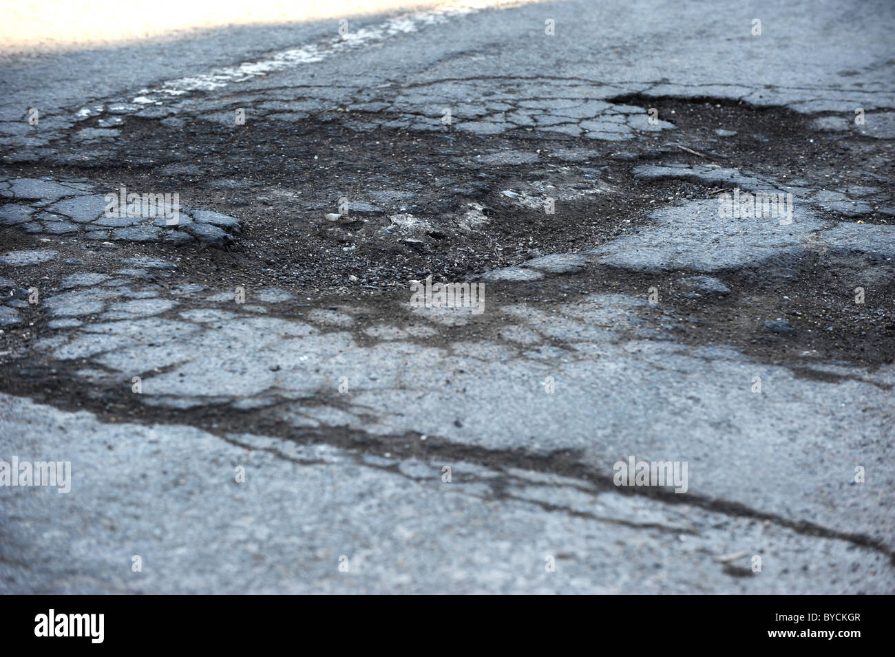 Deep potholes in a busy road caused by the recent snow and freezing weather - Stock Image