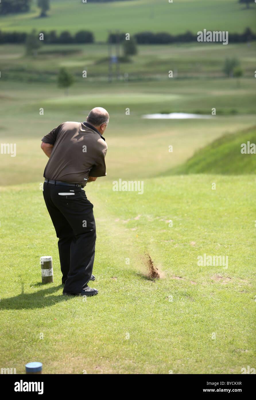 Golfer in brown shirt teeing off down fairway - Stock Image