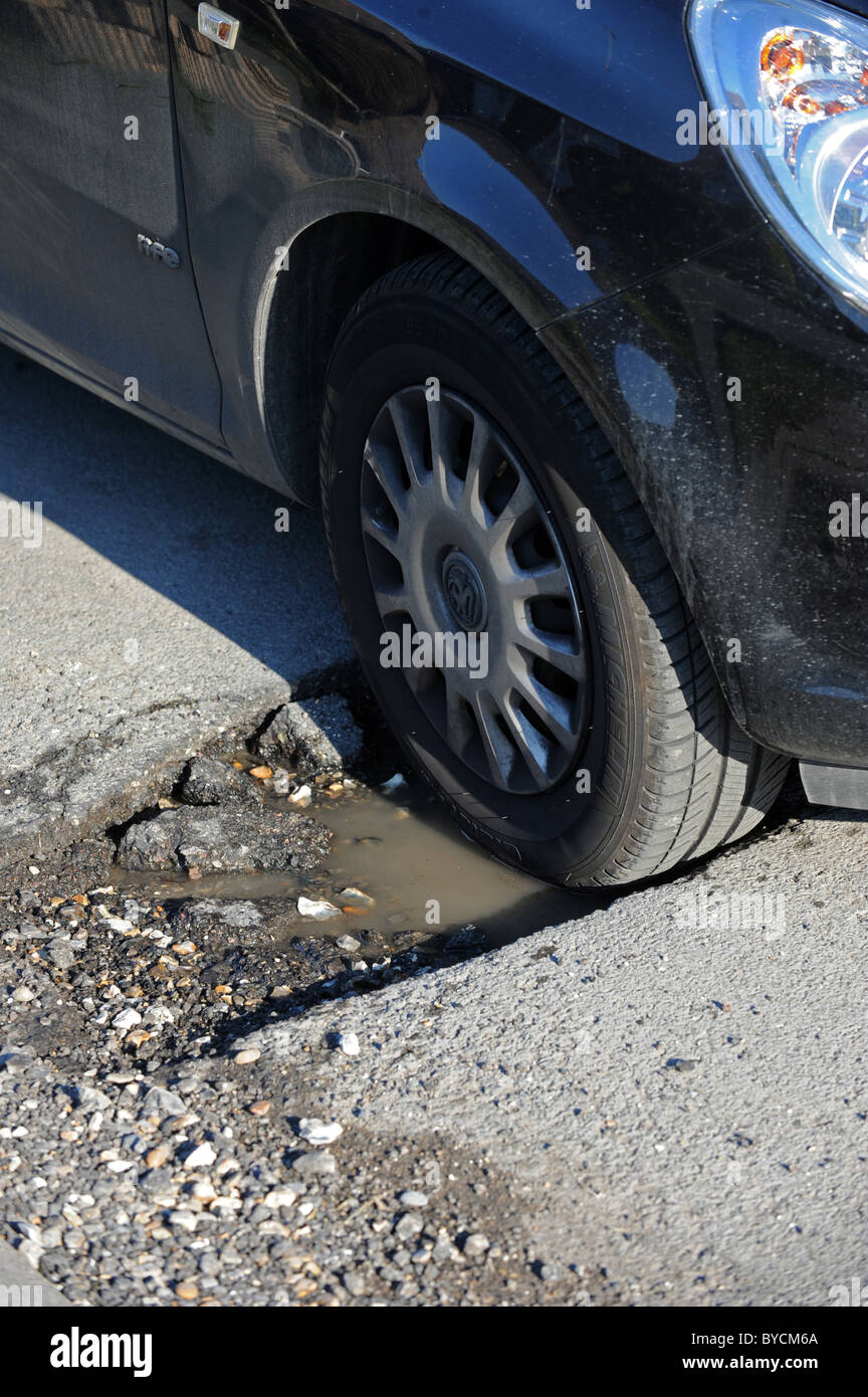A car tyre sits in a deep pothole in a busy road caused by the recent snow and freezing weather - Stock Image