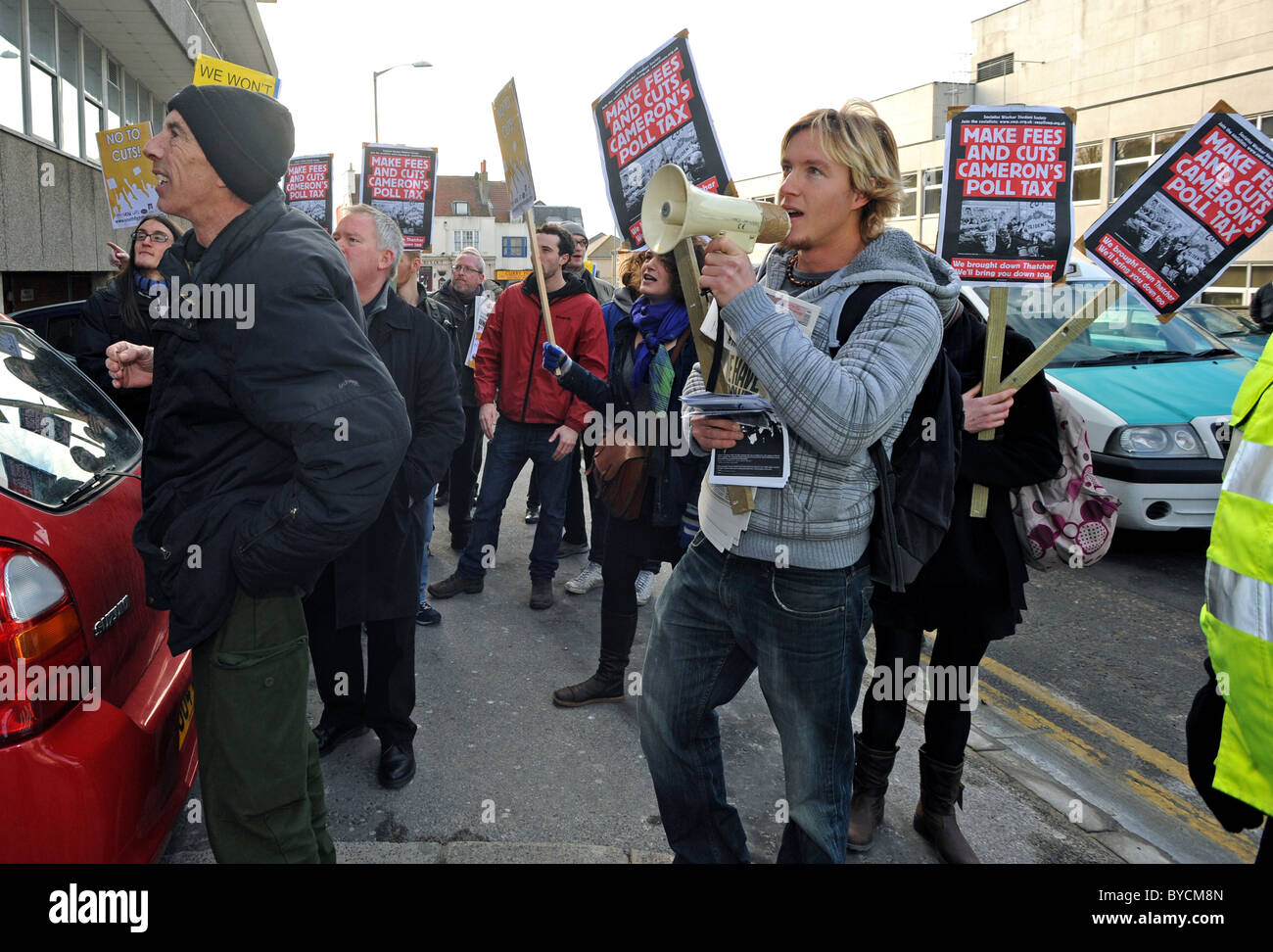 A small group of protestors shout at Employment Minister Chris Grayling during a visit to a Job Centre in Brighton - Stock Image