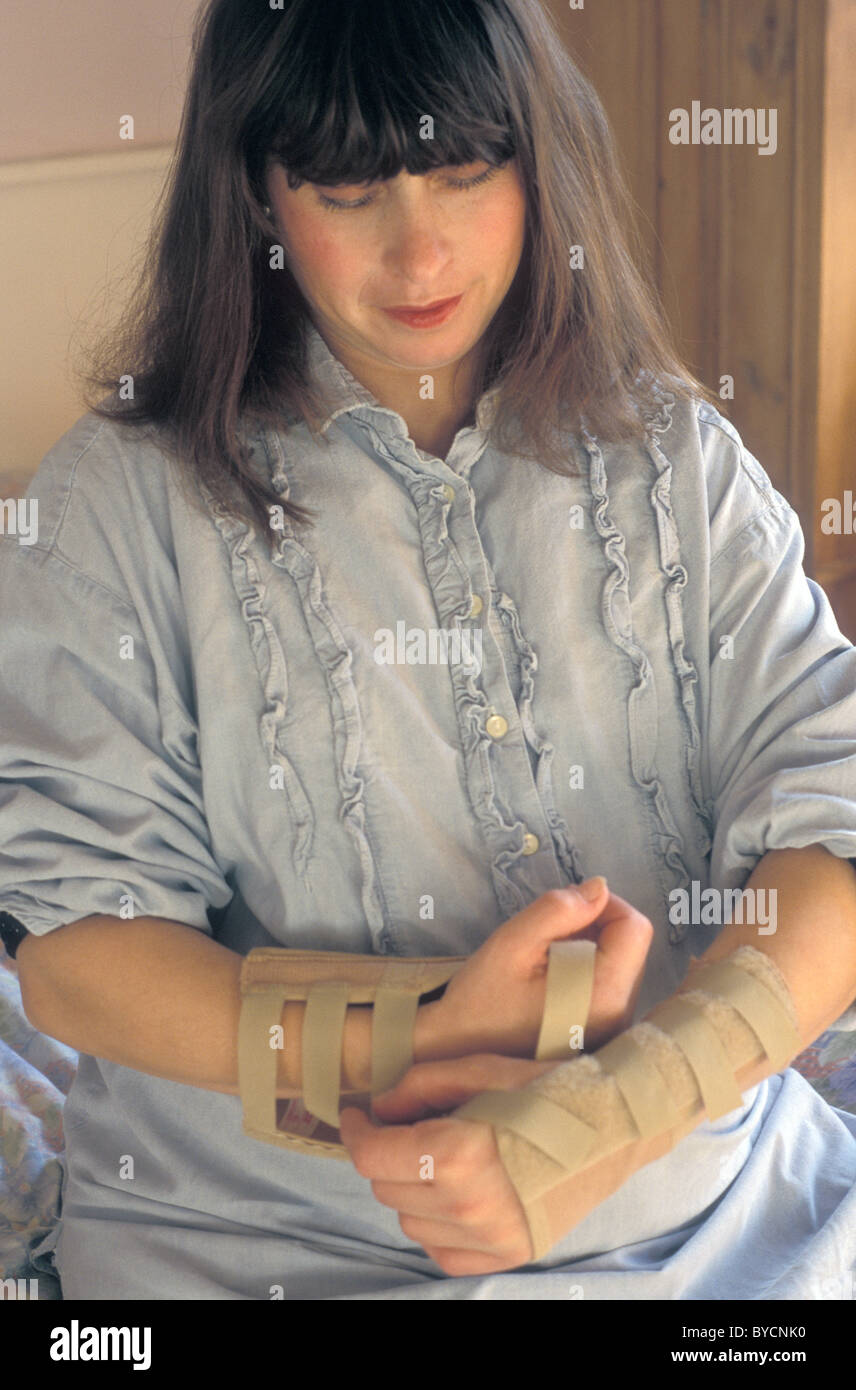 pregnant woman putting wristbands to ease carpel tunnel syndrome - Stock Image