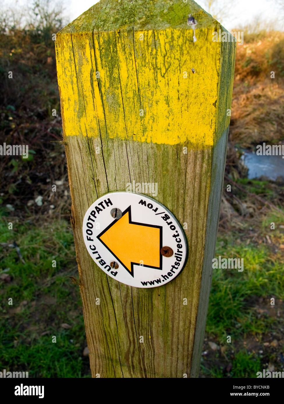 Public footpath sign with yellow arrow on a wooden post by the footpath by The River Stort in Harlow, Essex, UK - Stock Image