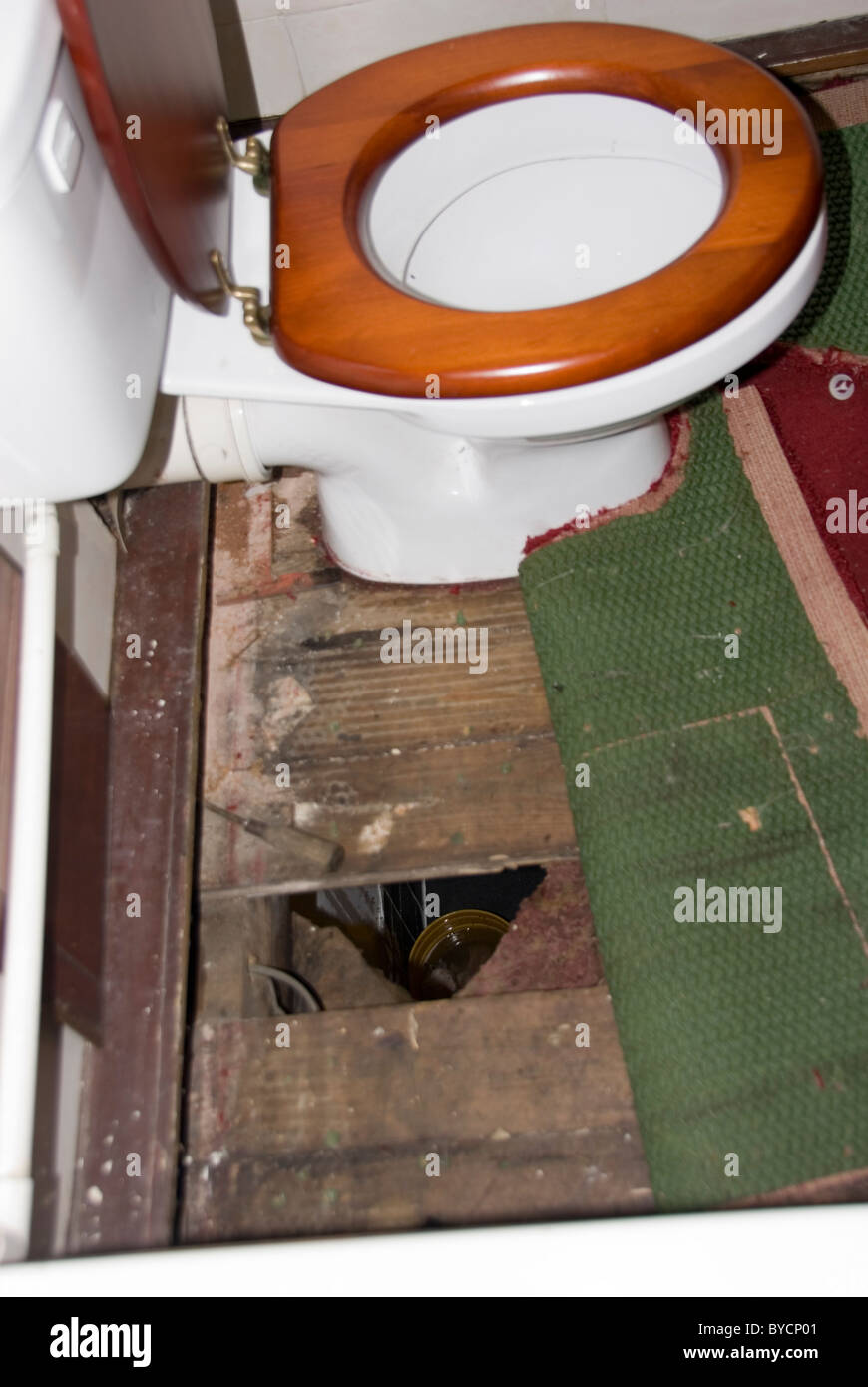 Carpet Rolled Back Floor Boards Lifted in Toilet to Reveal