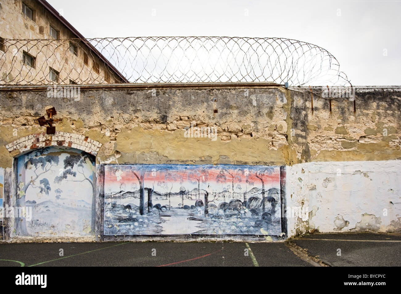 Grim walls of the exercise yard topped with razor wire and decorated with Australian bush scenes at Fremantle prison - Stock Image