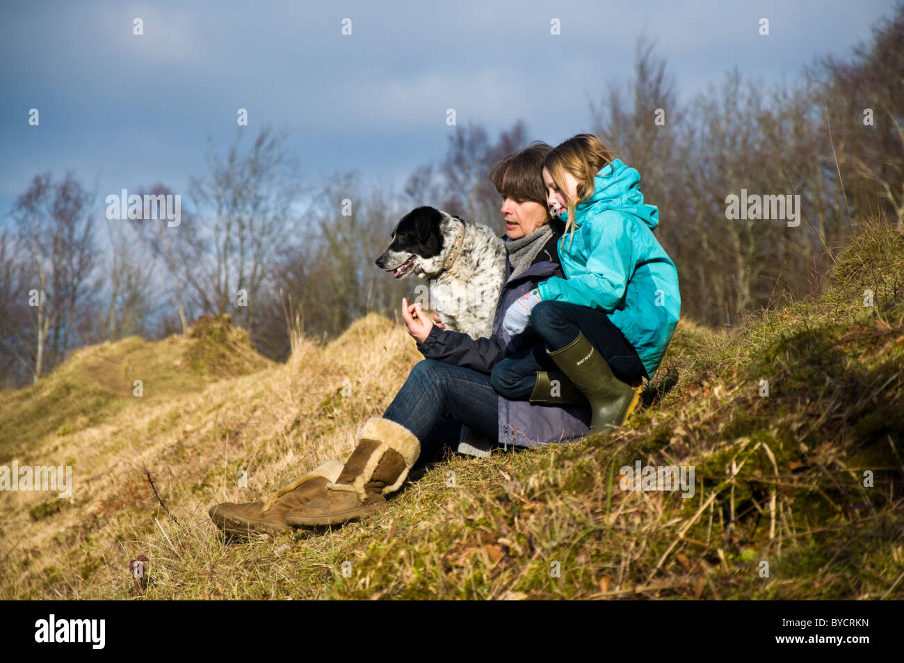 Mother and daughter chat pet dog sits beside them on a country walk - Stock Image