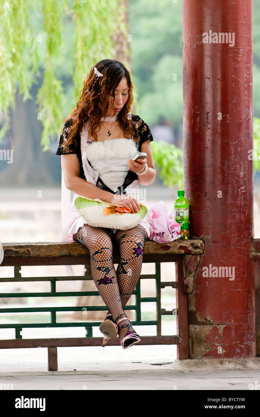 1299ca8bca547 Contemporary Chinese young woman with permed hair fishnet tights and  interesting fashion at New Summer Palace