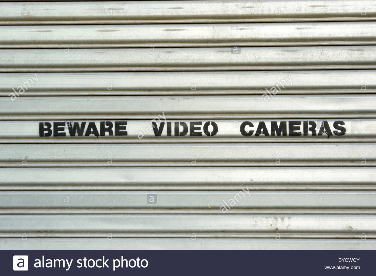 Beware Video Cameras sign on metal security shutters, USA - Stock Image