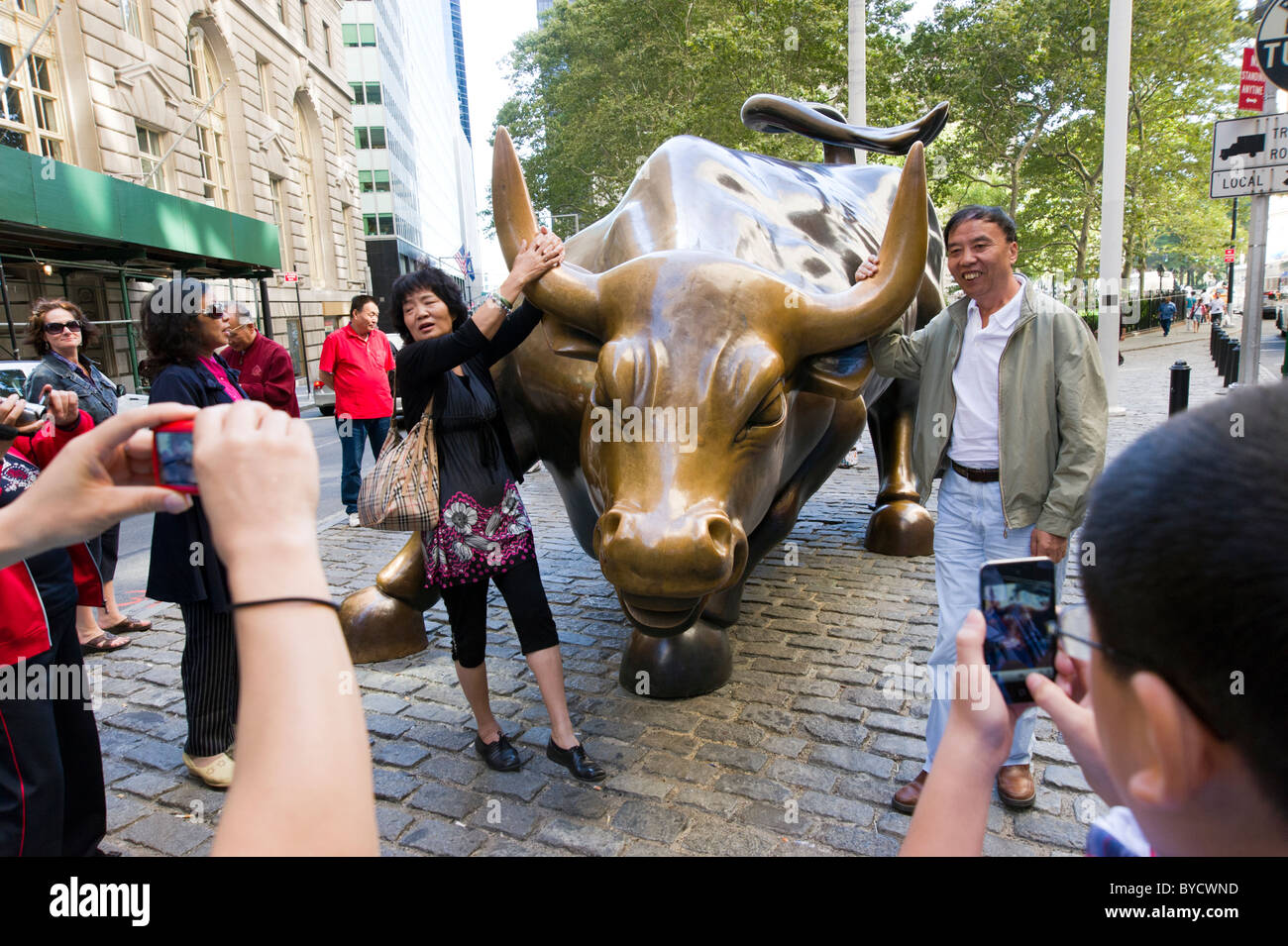 Tourists posing for photos besides the charging bull sculpture close to Wall Street , New York City, America, USA - Stock Image