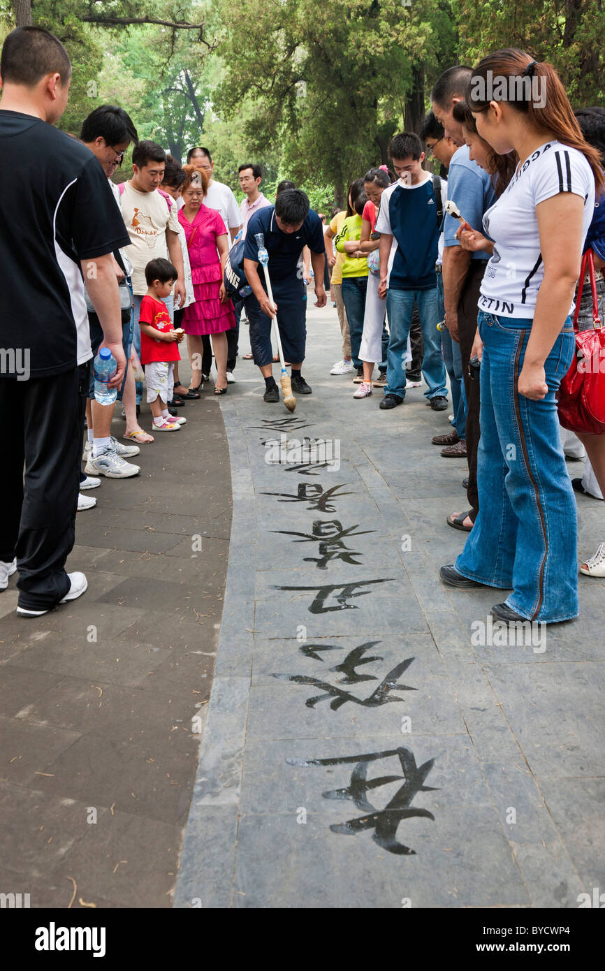 Chinese man practicing street calligraphy in the grounds of the New Summer Palace, Beijing, China. JMH4795 - Stock Image