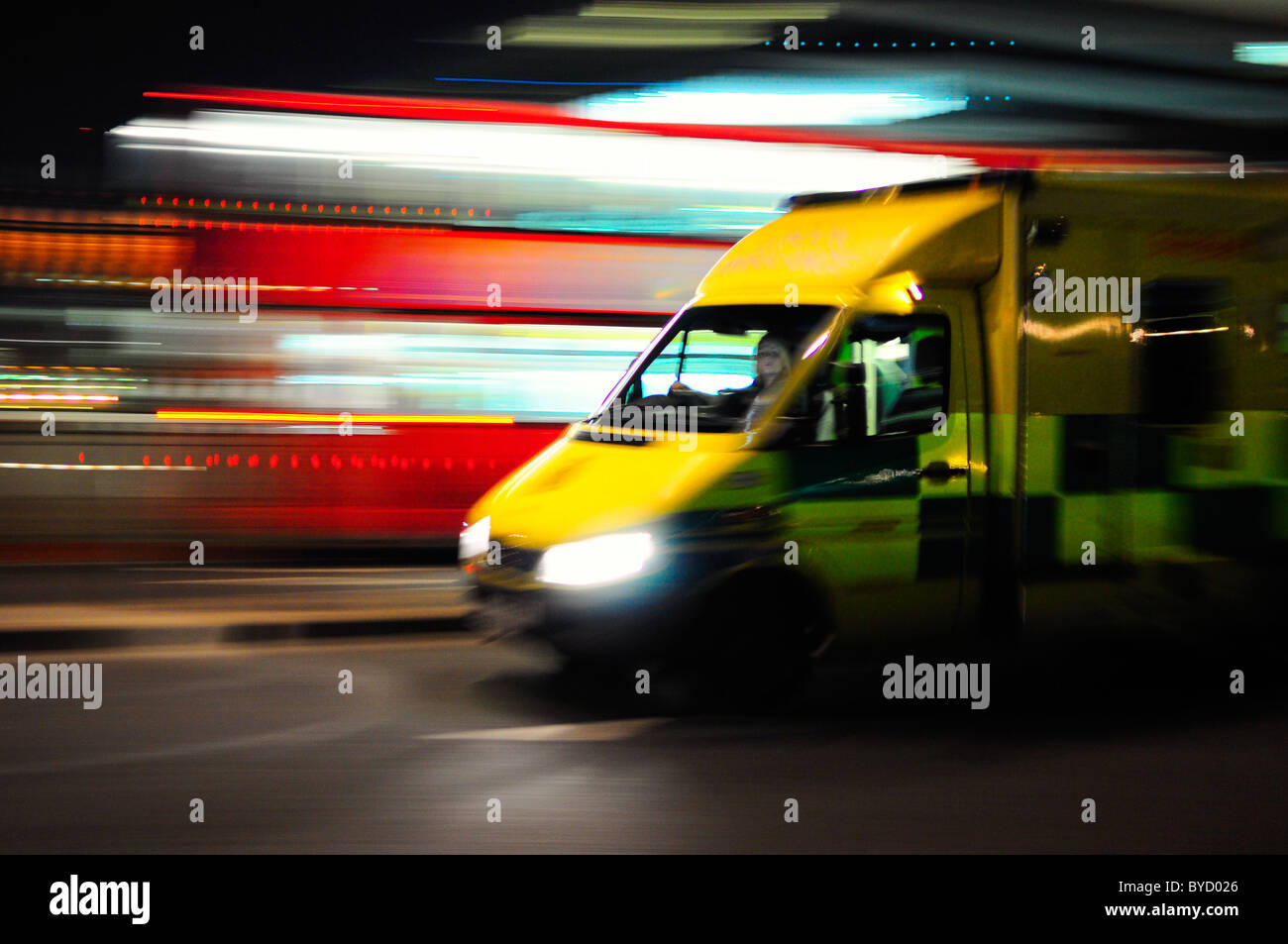 Ambulance rushing past a red bus with motion blur - Stock Image