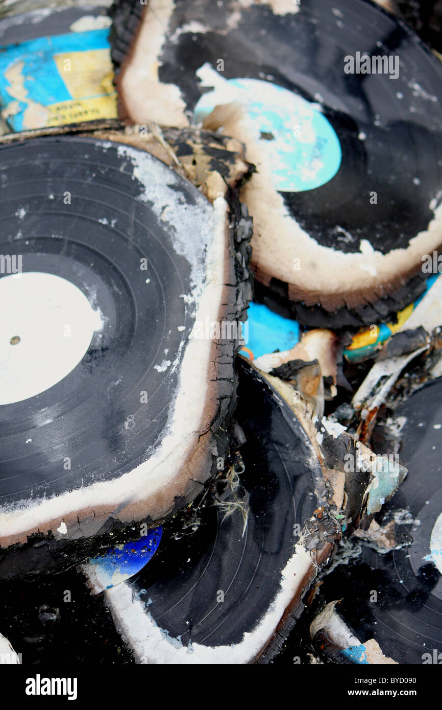 A selection of music records which have been warped and burnt due to fire damage - Stock Image