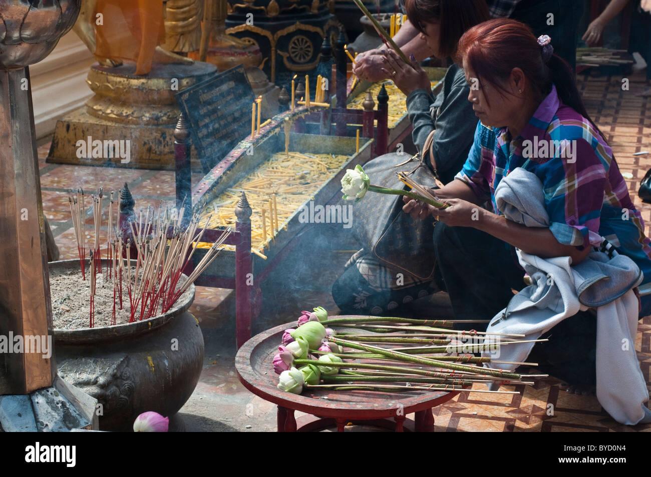 Worshiper placing candles, Wat Phra That Doi Suthep, Chiang Mai, Thailand - Stock Image