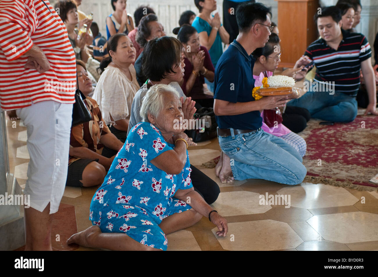 Worshipers at Wat Traimit, China Town, Bangkok, Thailand - Stock Image