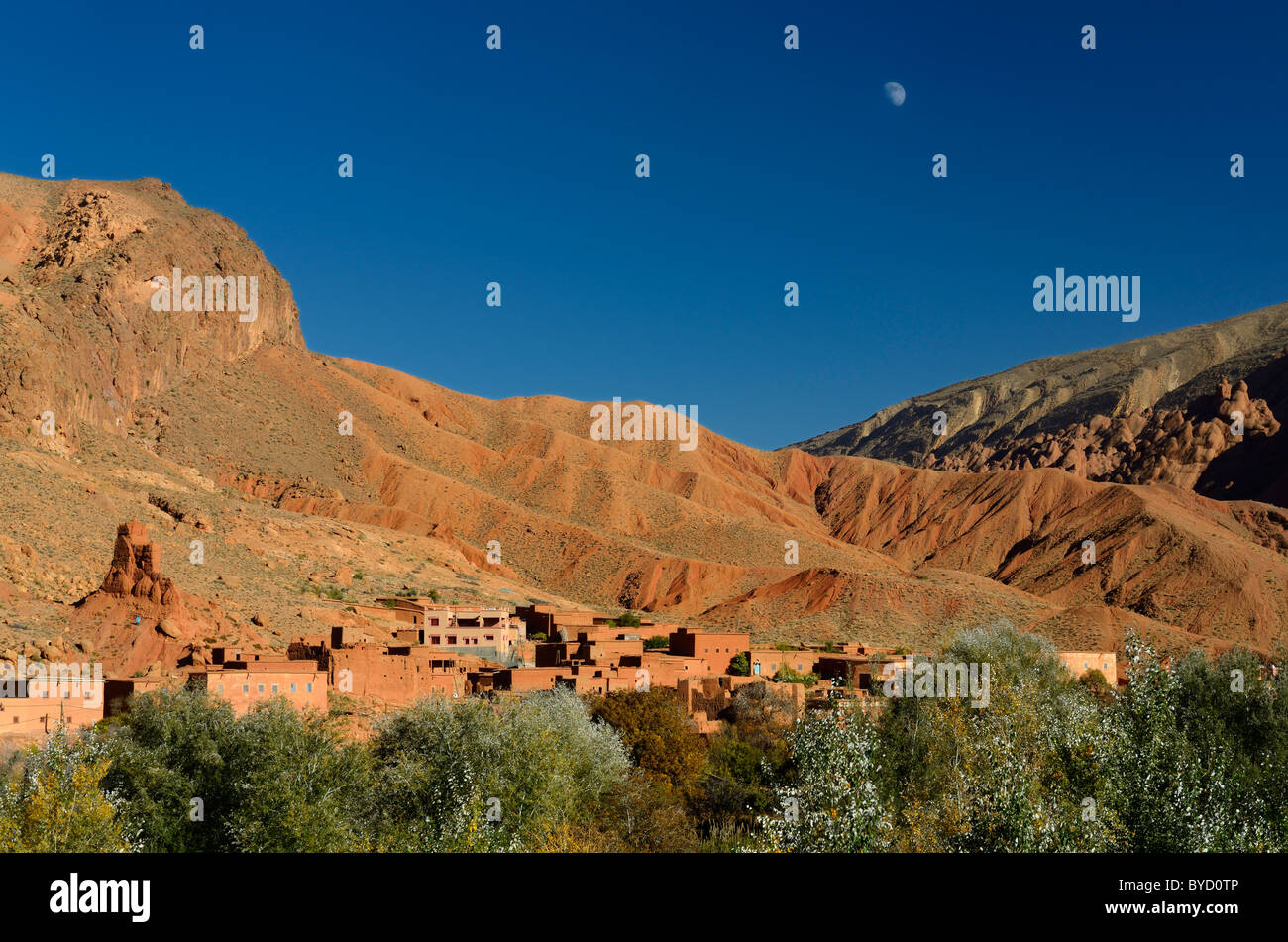 Moon in blue sky over red soil and rock formations in Dades Gorge Morocco - Stock Image