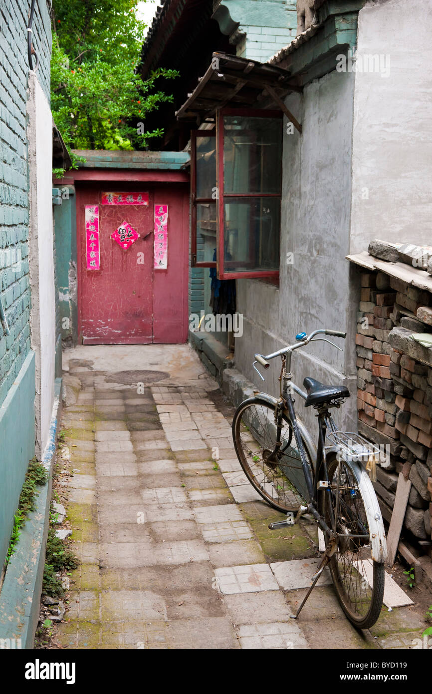 Alleyway with bicycle leading to door of house in the Hutong, Beijing, China. JMH4842 - Stock Image