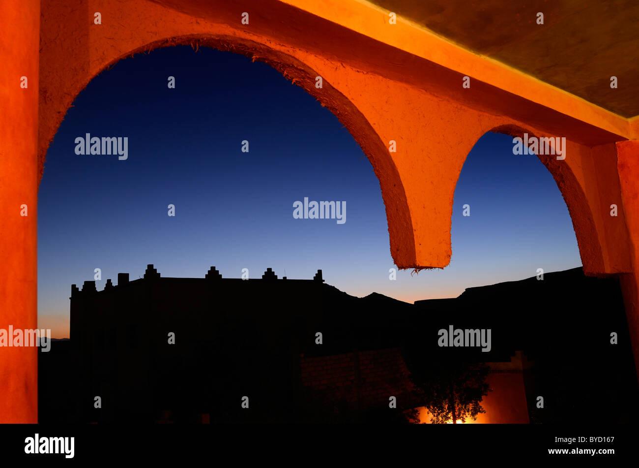 Orange adobe mud and straw resort arches with indigo sunset in Tinerhir Morocco - Stock Image