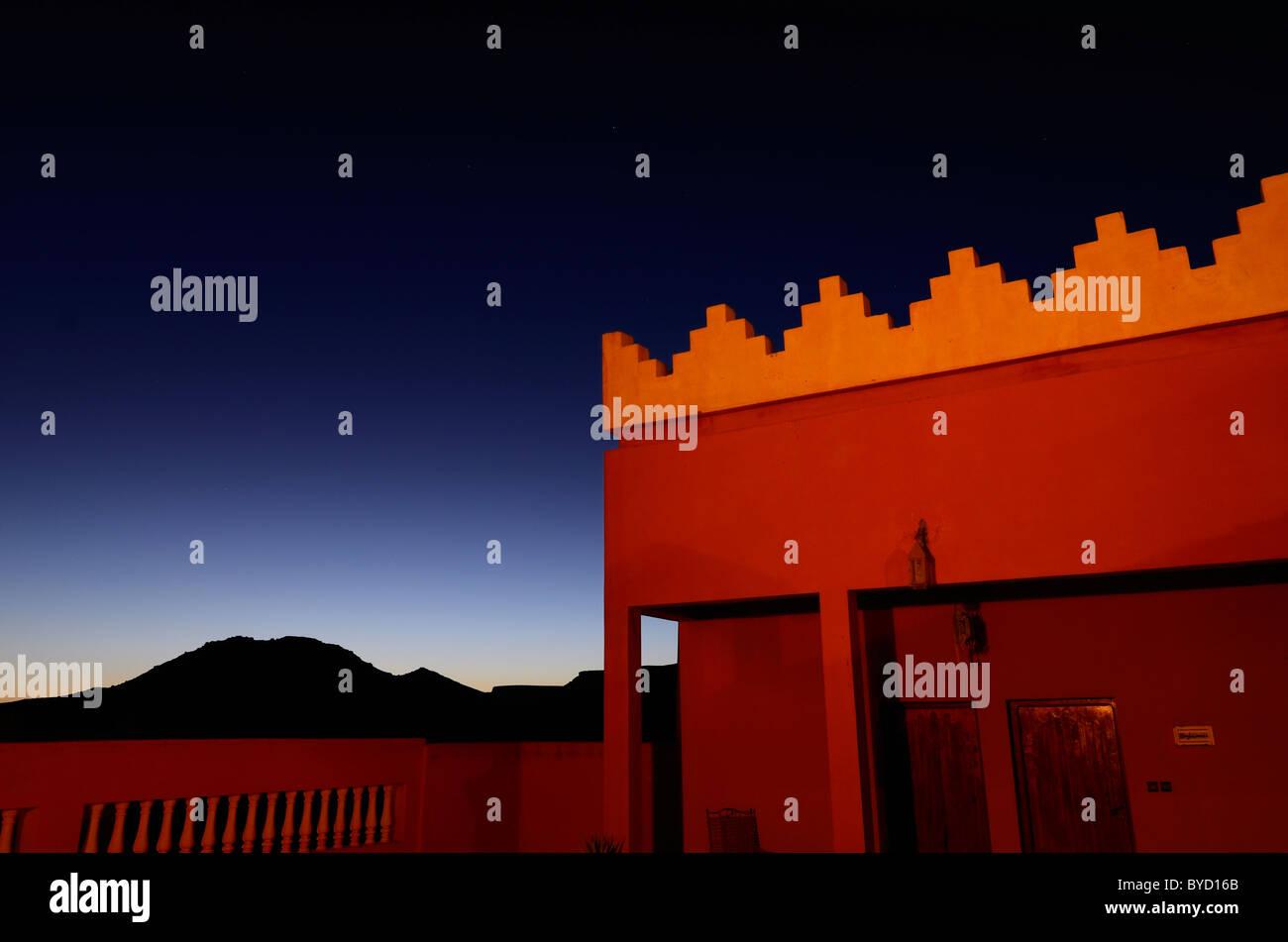 Orange adobe crenelations on rooftop of resort with indigo sunset at twilight in Tinerhir Morocco - Stock Image