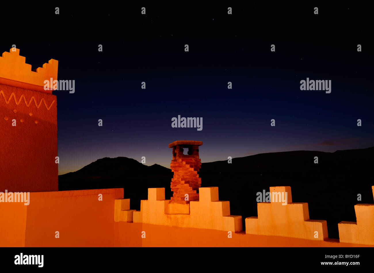 Adobe crenelations and chimney in gold light on rooftop of resort with indigo sunset at twilight in Tinerhir Morocco - Stock Image