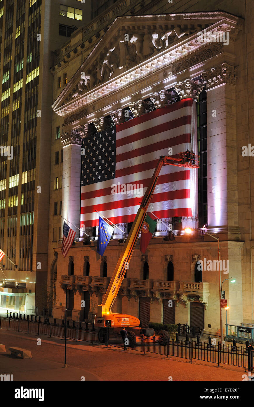 Crane and workers putting up large flags on the New York Stock Exchange in New York City. May 26, 2010. - Stock Image
