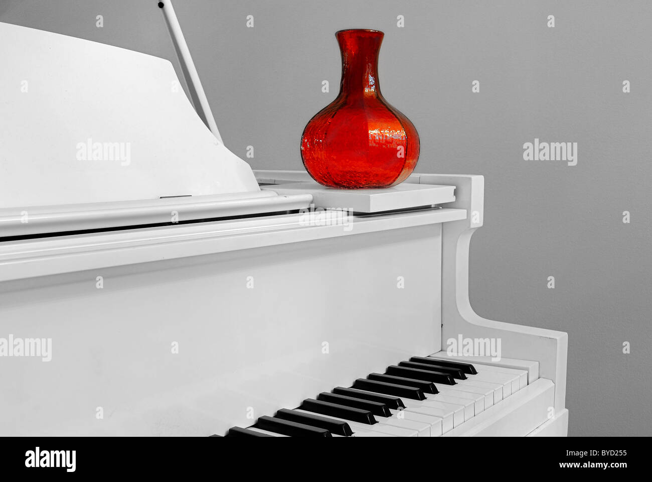 Corner of a piano with a red vase in a home interior. - Stock Image