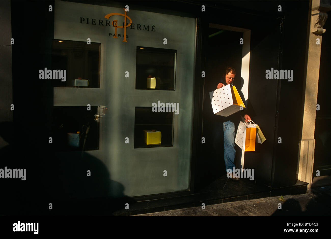A shopper laden with shopping bags emerges from the Paris chocolatier shop Pierre Hermé on Rue Vaugirard. - Stock Image