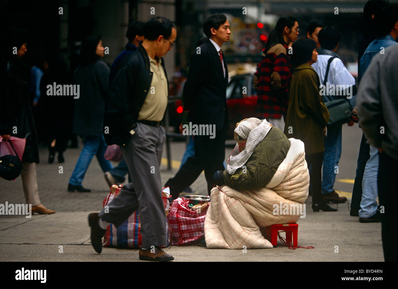 Passers-by ignore destitute bag-lady in Hong Kong's Tsim Sha Tsui street on the Kowloon side. - Stock Image