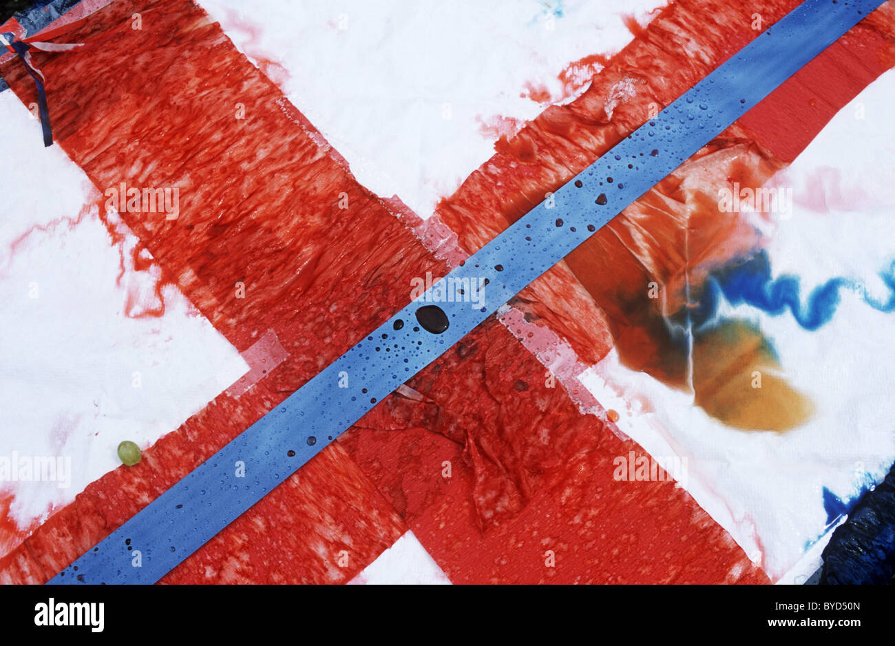 Running colours of a table paper covering, rained on and spoiled after unseasonal rain during patriotic VE Day street - Stock Image