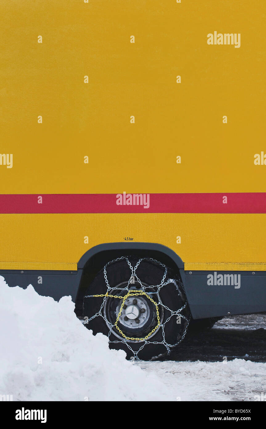 Van with mounted snow chains on a wintry road - Stock Image