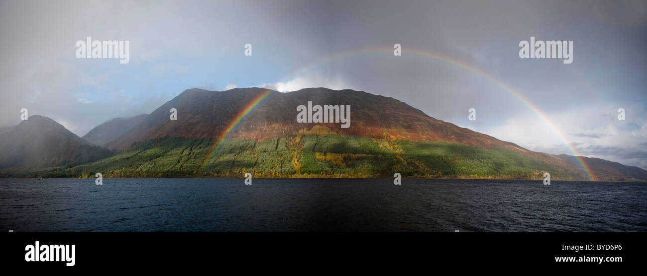 A rainbow arches over a lake in a mountainous landscape. Stock Photo