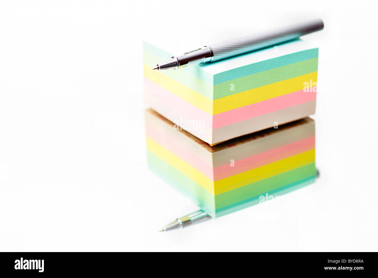 Pen lying on a colourful notepad - Stock Image