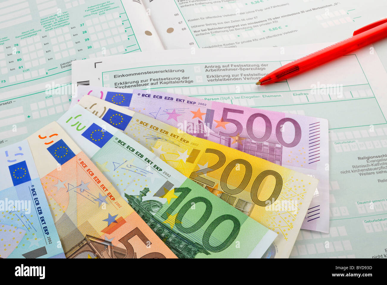 Fan of various euro banknotes and a pen on the forms of an income tax return, symbolic image for a tax burden, income - Stock Image